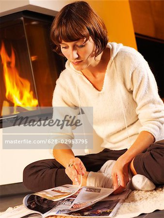 Young woman reading magazine by the fireside Stock Photo - Premium Royalty-Free, Image code: 628-02953795