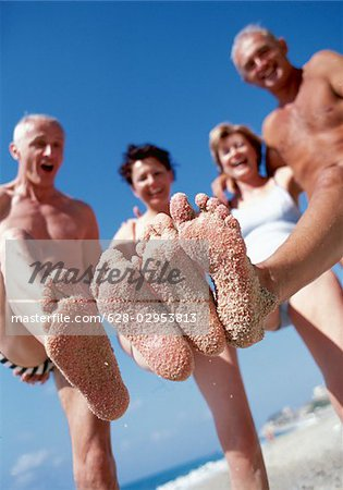 Two senior couples on the beach with sand on their feet Stock Photo - Premium Royalty-Free, Image code: 628-02953813