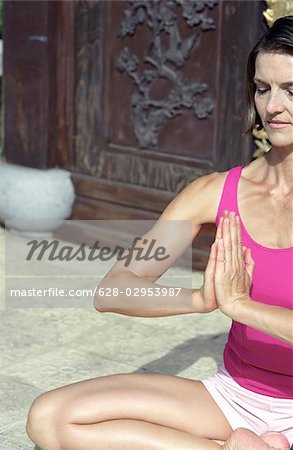 Darkhaired Woman in a  Buddha-Sit-Position  - Yoga - Meditation - Posture Stock Photo - Premium Royalty-Free, Image code: 628-02953987