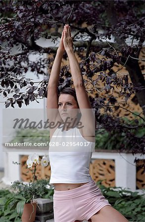 Darkhaired Woman lifting her Arms up - Yoga - Plants - Garden Stock Photo - Premium Royalty-Free, Image code: 628-02954017