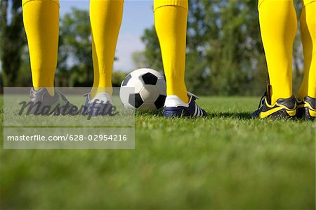 Three soccer players standing side by side Stock Photo - Premium Royalty-Free, Image code: 628-02954216