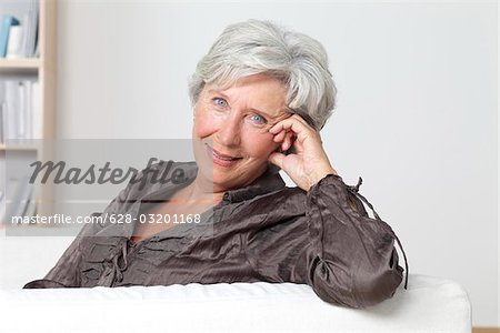 Confident senior woman on couch Stock Photo - Premium Royalty-Free, Image code: 628-03201168