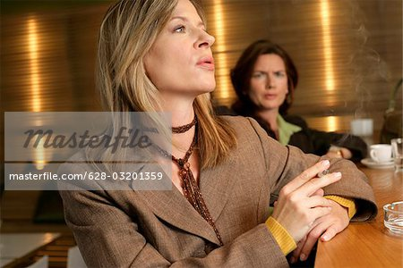Woman feeling disordered of a smoking woman Stock Photo - Premium Royalty-Free, Image code: 628-03201359