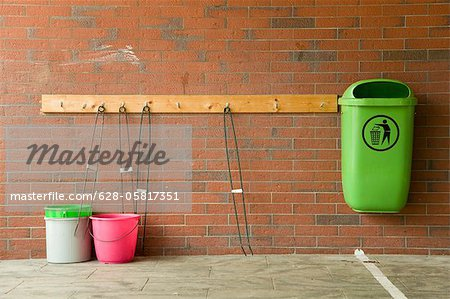 Green trash can and buckets at brick wall, Hamburg, Germany Stock Photo - Premium Royalty-Free, Image code: 628-05817351