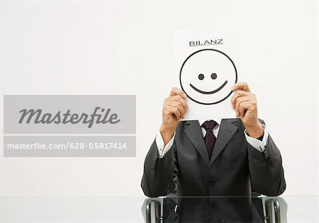 "Businessman holding a piece of paper in front of his face with a smiley on it and letters saying ""Bilanz"" Stock Photo - Premium Royalty-Free, Image code: 628-05817414"