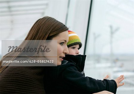 Mother and son looking out, Munich airport, Bavaria, Germany Stock Photo - Premium Royalty-Free, Image code: 628-05817422