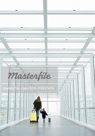 Mother and son walking with baggage through a passage, Munich airport, Bavaria, Germany Stock Photo - Premium Royalty-Free, Image code: 628-05817425