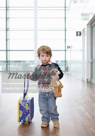 A shy boy with a soft toy and a trolley on an airport Stock Photo - Premium Royalty-Free, Image code: 628-05817426
