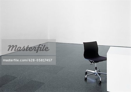 Office chair and desk in an empty room Stock Photo - Premium Royalty-Free, Image code: 628-05817457
