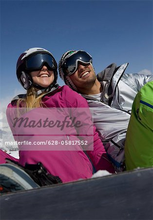 Young couple with snowboard sitting in snow Stock Photo - Premium Royalty-Free, Image code: 628-05817552