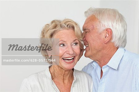 Senior couple whispering Stock Photo - Premium Royalty-Free, Image code: 628-05817564