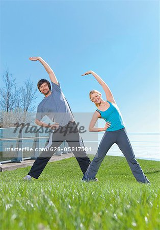 Man and woman doing gymnastics in meadow Stock Photo - Premium Royalty-Free, Image code: 628-05817584