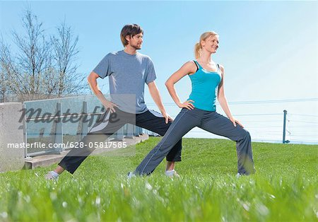 Man and woman doing gymnastics in meadow Stock Photo - Premium Royalty-Free, Image code: 628-05817585