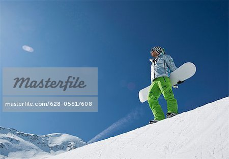 Man standing with snowboard at halfpipe Stock Photo - Premium Royalty-Free, Image code: 628-05817608