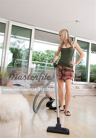 Young woman vacuum cleaning while man listening to music Stock Photo - Premium Royalty-Free, Image code: 628-05817614