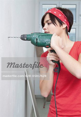 Young woman drilling with electric drill Stock Photo - Premium Royalty-Free, Image code: 628-05817628