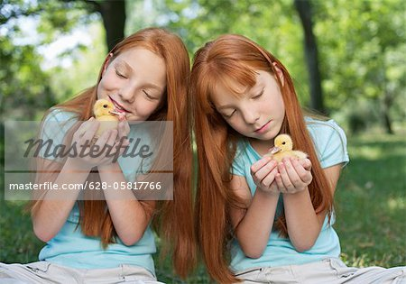 Red haired twins holding chicks Stock Photo - Premium Royalty-Free, Image code: 628-05817766