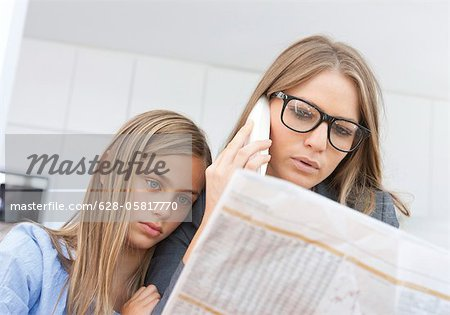 Mother reading newspaper and phoning with daughter by her side Stock Photo - Premium Royalty-Free, Image code: 628-05817770