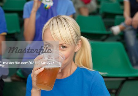 Female fan drinking beer in a stadium Stock Photo - Premium Royalty-Free, Image code: 628-05817773