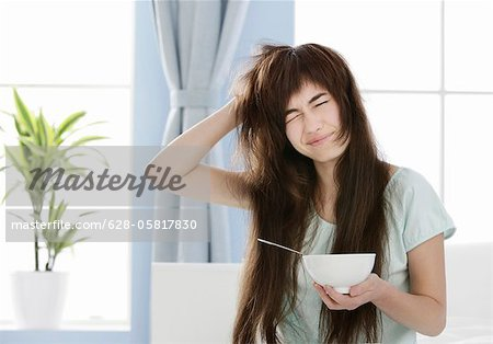 Young woman with muesli bowl disheveling her hair Stock Photo - Premium Royalty-Free, Image code: 628-05817830