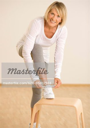 Woman lacing sport shoe in gymnasium Stock Photo - Premium Royalty-Free, Image code: 628-05817966