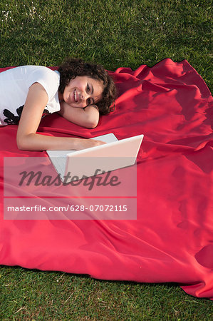 Girl using laptop on blanket Stock Photo - Premium Royalty-Free, Image code: 628-07072115