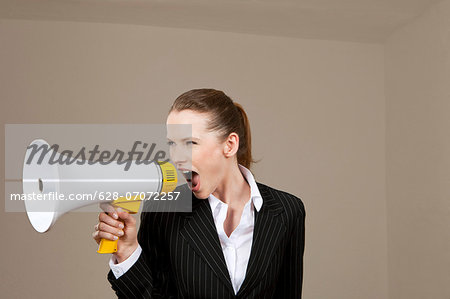 Businesswoman screaming into megaphone Stock Photo - Premium Royalty-Free, Image code: 628-07072257