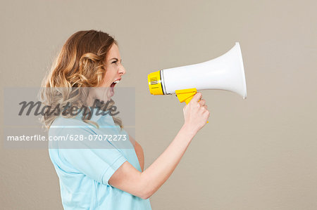 Young woman screaming into megaphone Stock Photo - Premium Royalty-Free, Image code: 628-07072273