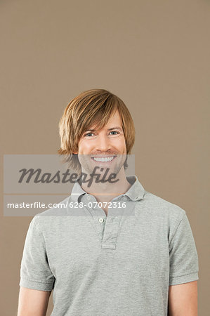 Smiling man in gray polo shirt Stock Photo - Premium Royalty-Free, Image code: 628-07072316
