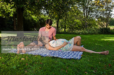 Man and pregnant woman on a blanket in a park Stock Photo - Premium Royalty-Free, Image code: 628-07072353