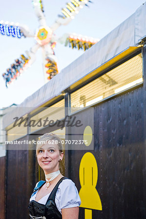 Woman standing in front of the women's restroom on the Oktoberfest in Munich, Bavaria, Germany Stock Photo - Premium Royalty-Free, Image code: 628-07072375