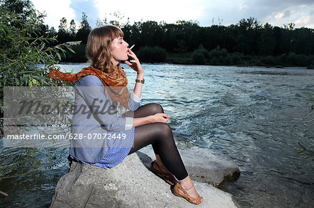 Young woman smoking a cigarette by the riverside Stock Photo - Premium Royalty-Free, Image code: 628-07072449