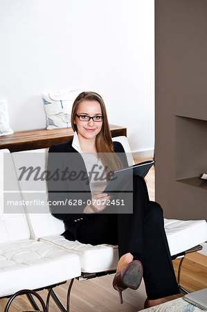 Smiling teenage girl holding folder Stock Photo - Premium Royalty-Free, Image code: 628-07072451