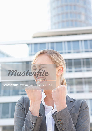 Happy businesswoman clenching fists Stock Photo - Premium Royalty-Free, Image code: 628-07072530