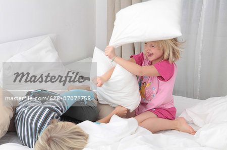 Brother and sister having a pillow fight in bed Stock Photo - Premium Royalty-Free, Image code: 628-07072758