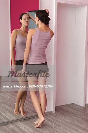 Brunette young woman in lingerie looking in mirror Stock Photo - Premium Royalty-Free, Image code: 628-07072784