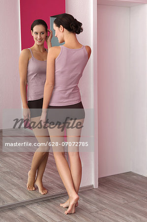 Brunette young woman in lingerie looking in mirror Stock Photo - Premium Royalty-Free, Image code: 628-07072785