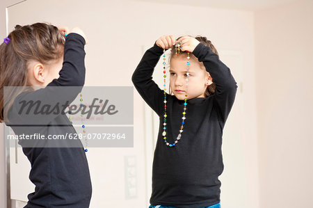 Girl with necklace looking in mirror Stock Photo - Premium Royalty-Free, Image code: 628-07072964