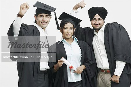 Portrait of two young men and a young woman in graduation gowns ...