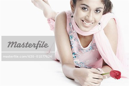 High angle view of a young woman lying down holding a flower Stock Photo - Premium Royalty-Free, Image code: 630-01077624