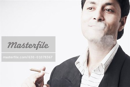 Close-up of a businessman smoking a cigar Stock Photo - Premium Royalty-Free, Image code: 630-01078367