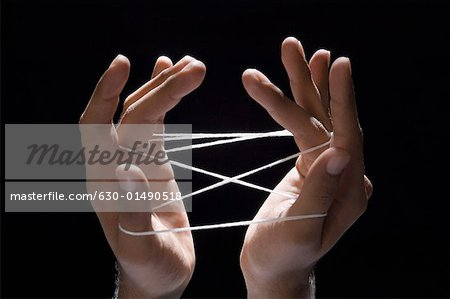 Close-up of a person's hands playing cats cradle with a rubber band Stock Photo - Premium Royalty-Free, Image code: 630-01490518