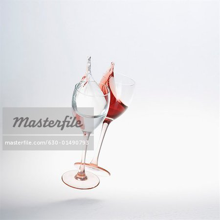 Close-up of wine spilling from two wine glasses Stock Photo - Premium Royalty-Free, Image code: 630-01490793