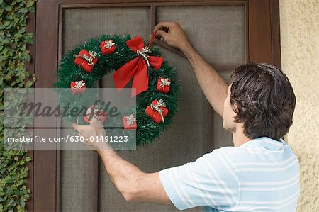Rear view of a young man hanging wreath on a door Stock Photo - Premium Royalty-Free, Image code: 630-01491223