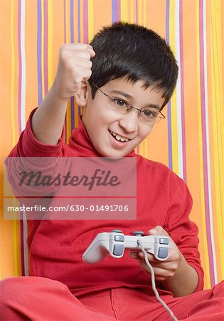 Close-up of a boy holding a joystick and raising his hand Stock Photo - Premium Royalty-Free, Image code: 630-01491706