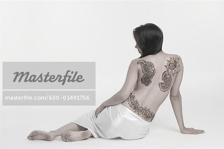 Rear view of a young woman with a tattoo on her back Stock Photo - Premium Royalty-Free, Image code: 630-01491756