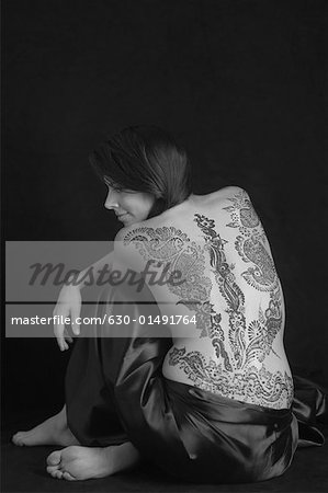 Rear view of a young woman with a tattoo on her back Stock Photo - Premium Royalty-Free, Image code: 630-01491764