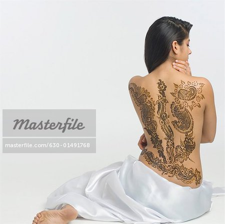 Rear view of a young woman with a tattoo on her back Stock Photo - Premium Royalty-Free, Image code: 630-01491768
