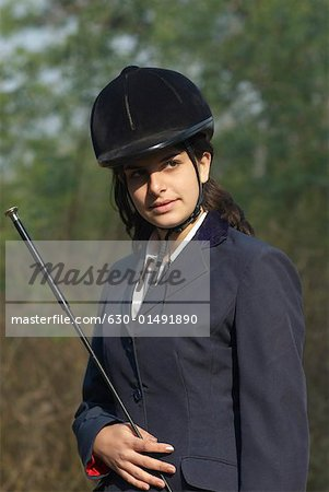 Close-up of a female jockey holding a riding crop Stock Photo - Premium Royalty-Free, Image code: 630-01491890
