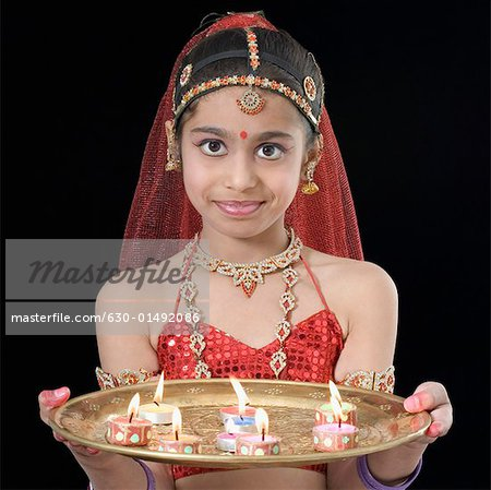 Portrait of a girl holding a plate of burning candles Stock Photo - Premium Royalty-Free, Image code: 630-01492086